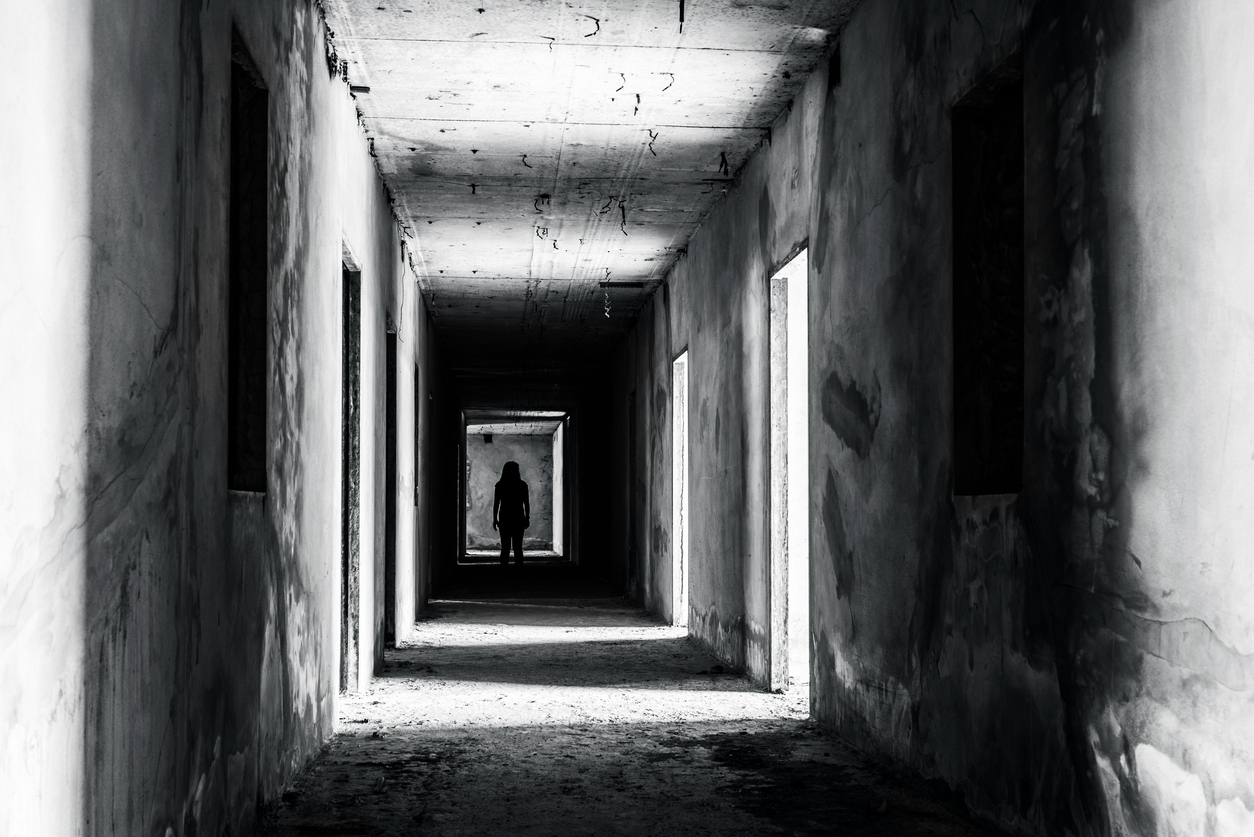 walkway in abandoned building with scary woman inside