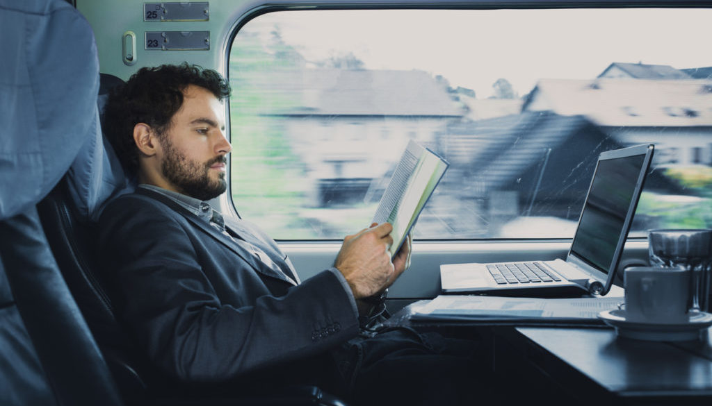 . bussinesman seating on a train  beside  window  and reading
