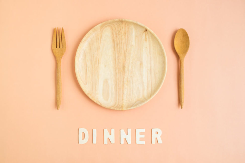 Top view of wooden cutlery with dinner word