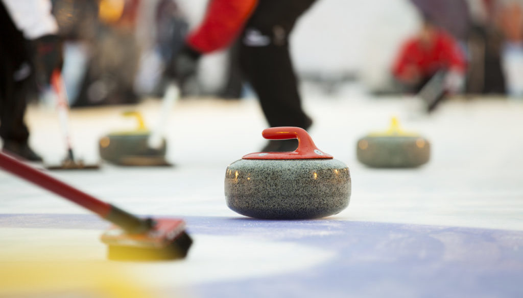 Sport of curling being played on a field
