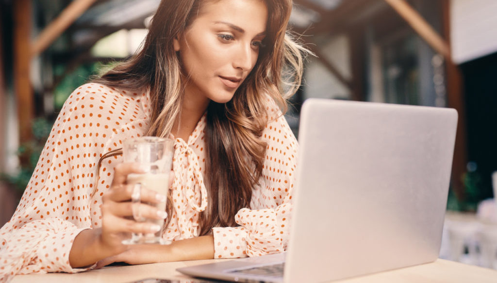 Young woman using a laptop at the cafe
