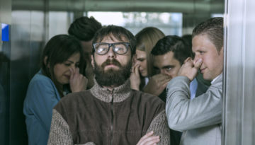 A dirty hipster affecting his coworkers in an elevator